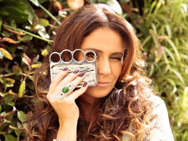 Giovanna faz graça com sua capinha de celular em forma de soco inglês (Foto: Salve Jorge/TV Globo)