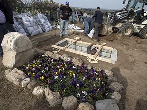Túmulo da segunda mulher de Sharon, Lily, à esq., ao lado de onde ele será enterrado, na fazenda da família em Havat Shikmin, perto da cidade israelense de Sderot (Foto: Jack Guez/AFP)