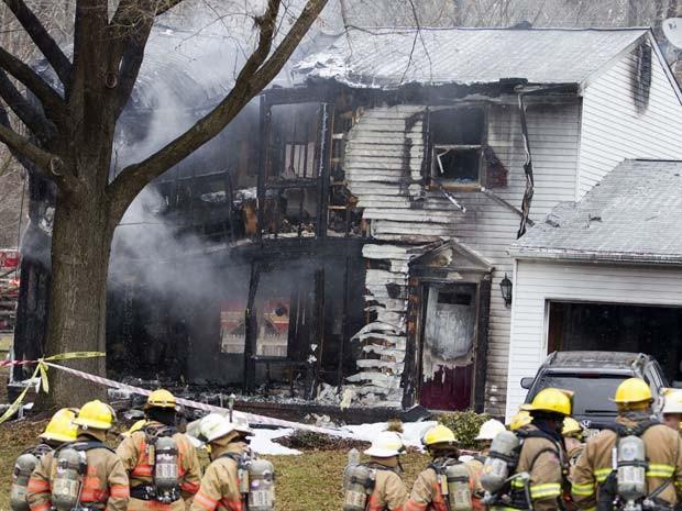 Bombeiros isolam casa em Gaithersbug em que avião pequeno caiu nesta segunda-feira (8); três pessoas morreram (Foto: AP Photo/Jose Luis Magana)