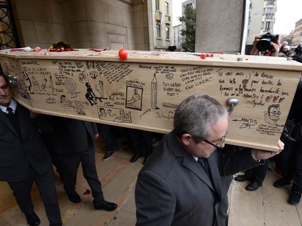 15/1 - Homens carregam o caixão do cartunista Bernard Verlhac, conhecido como Tignous, coberto por desenhos e mensagens, durante velório na prefeitura de Montreuil, perto de Paris (Foto: Bertrand Guay/AFP)