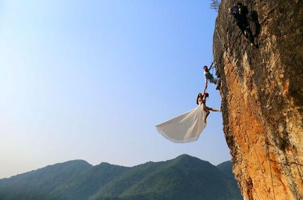 Alpinista amador, o chinês Zheng Feng posou para fotos de casamento com sua noiva em penhasco (Foto: China Daily/Reuters)