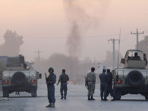 Policiais afegãos montam guarda no local de um ataque talibã no sábado (30). Pelo menos três pessoas morreram e dezenas ficaram feridas quando um carro-bomba e atiradores atacaram um escritório da agência de inteligência afegã  (Foto: Parwiz/Reuters)