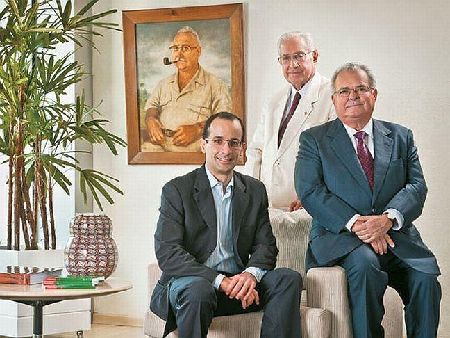 Norberto Odebrecht entre seu filho Emílio e o neto Marcelo e com a imagem do pai, o pioneiro Emílio Odebrecht, ao fundo (Foto: Divulgação)