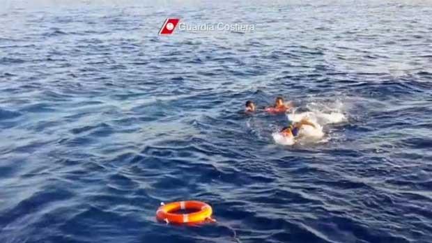 Imagem de um vídeo divulgaod pela Guarda Costeira mostra um salva-vidas pulando no mar para recuperar os sobreviventes do navio  (Foto: Guarda Costeira da Itália/ AP)