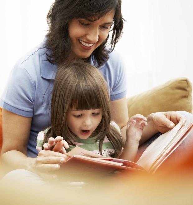 Mãe e filha com um livro em mãos (Foto: Thinkstock)