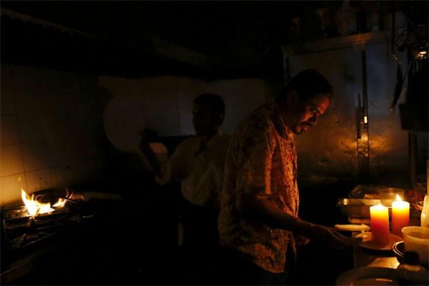 Funcionários na cozinha de restaurante de Caracas tenham completar pedidos durante apagão (Foto: Reuters/Carlos Garcia Rawlins)