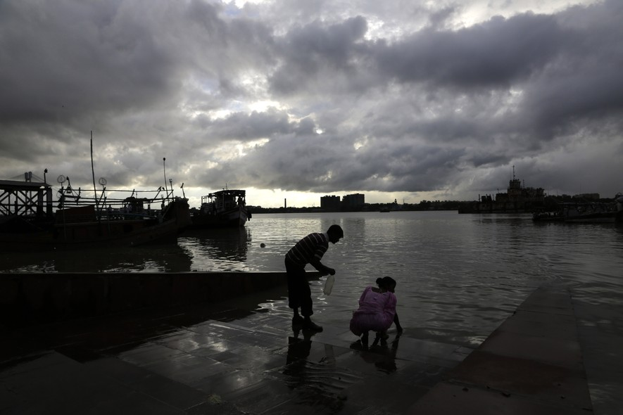Monsoon clouds hover over as a couple fetch water from the Ganges river, holy to Hindus, in Kolkata, India, Sunday, Aug. 31, 2014. India's monsoon season runs from June to September. (AP Photo/ Bikas Das)