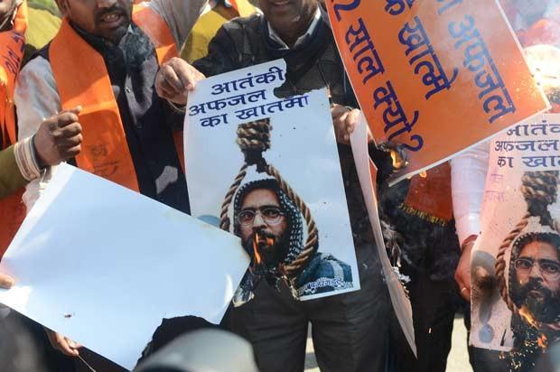 Cartazes com rosto de Mohammed Afzal Guru são queimados após sua execução neste sábado (9) em Nova Déli, na Índia (Foto: AP)
