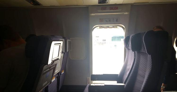 A porta da aeronave aberta pela passageira