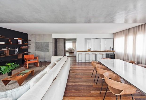 A madeira de demolição cobre todo o piso do living e também do hall do elevador e de circulação. Atrás da parede com espelho fica o lavabo, à esquerda, o corredor para a área íntima e, à direita, a cozinha (Foto: Maíra Acayaba / Divulgação)