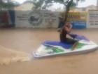 Jovem usa moto aquática em rua alagada pela chuva no RJ