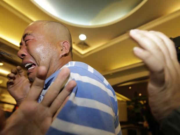 Parente de um passageiro do avião da Malaysian Airlines se desespera após ouvir anúncio que a aeronave caiu no mar (Foto: Jason Lee/Reuters)