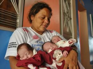Mãe segura os bebês no colo após alta hospitalar (Foto: André Ferreira/ G1)