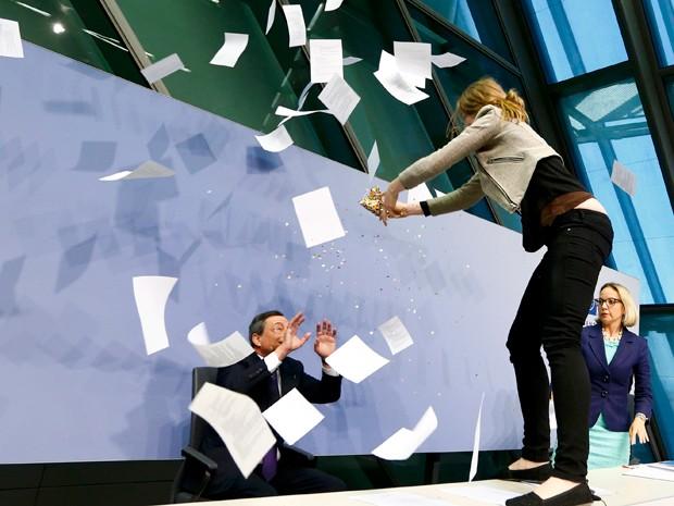 Mulher joga papeis e uma espécie de confete em cima do presidente do BCE (Foto: Reuters)