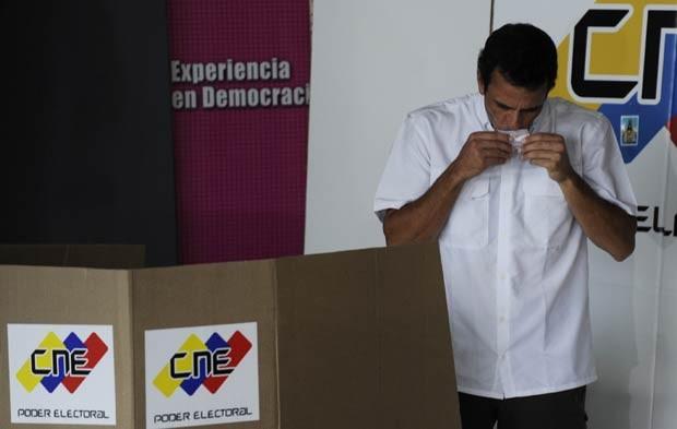 O candidato oposicionista à presidência da Venezuela, Henrique Capriles, beija o voto neste domingo (7) (Foto: AP)