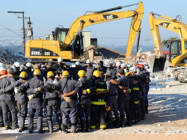 29/8 - Bombeiros se abraçam e são aplaudidos após localização do corpo da 10ª vítima (Foto: Adriano Lima/Brazil Photo Press/Estadão Conteúdo)
