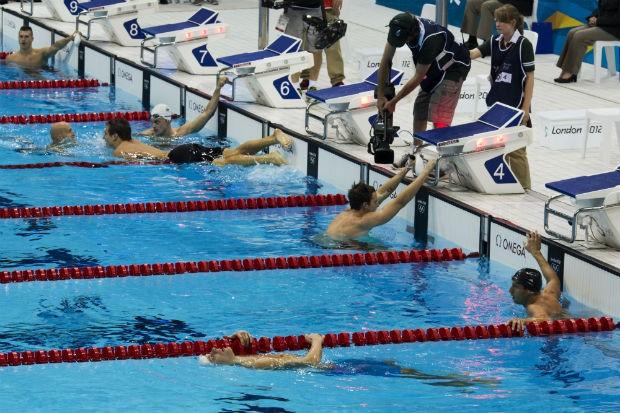 O americano Adrian Nathan (short preto) cumprimenta o canadense medalha de bronze Brent Hayden (careca, sem touca) enquanto o autraliano James Magnussen, medalha de prata, recebe atenção do cinegrafista oficial dos Jogos, na final dos 100m nado livre (Foto: Mauricio Lima/ÉPOCA)