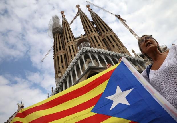 Mulher segura bandeira da Catalunha durante manifestação pela independência da região em Barcelona (Foto: Dan Kitwood/Getty Images)