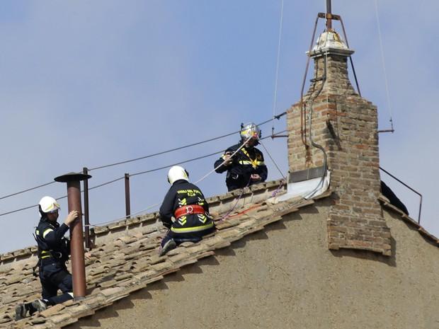 Funcionários do Corpo de Bombeiros trabalham na instalação de uma chaminé no teto da Capela Sistina, no Vaticano, neste sábado (9) (Foto: Max Rossi/Reuters)