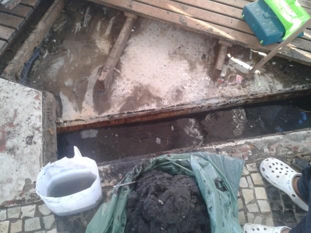 Água acumulada se mistura a areia. Por conta da falta de equipamentos, é retirada com as mãos e jogada diretamente no lixo (Foto: Julia Karam/Arquivo Pessoal)