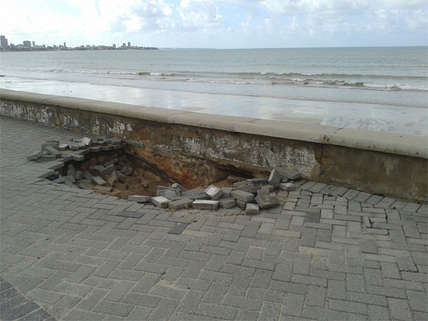 Na orla da Praia de Manaíra, o piso da calçadinha também está quebrado. O problema foi encontrado onde fica uma desembocadura de galeria de águas pluviais. O banco do local, no entanto, não cedeu (Foto: Krystine Carneiro/G1)
