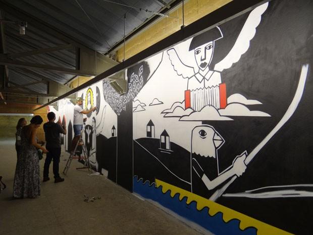 """Derlon Almeida pint, ao vivo, mural """"Ir e Vir"""". Ele usa basicamente spray para fazer desenho em parede de 14 metros de cumprimento. 'Usei músicas de Gonzaga para criar imagens', disse. (Foto: Luna Markman/ G1)"""