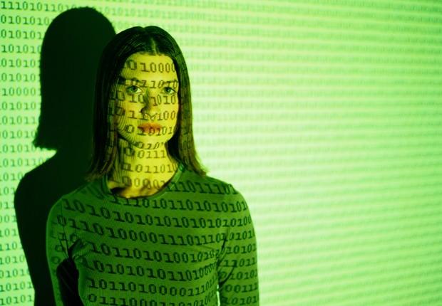 Mulher com projeção de código binário (Foto: Thinkstock)