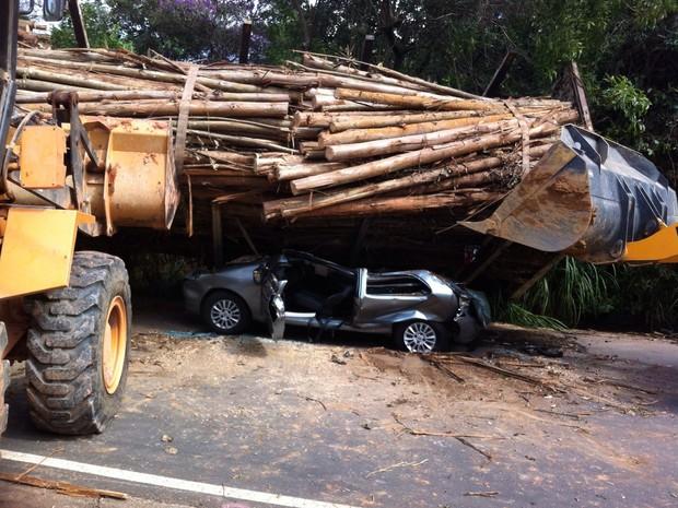 Caminhão carregado com tora de madeira tombou em cima de carro (Foto: Moisés Soares / TV TEM)