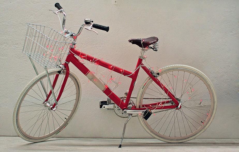 Enquanto não está em ação, a bicicleta adquire mais vida e cor. Estacionada no corredor de entrada do apartamento, a peça de alumínio teve o corpo e a roda traseira trespassados pelas luzinhas de LED vermelhas