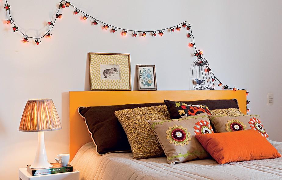 Para não ter de investir em marcenaria planejada no quarto, destaque outros detalhes da decoração. Aqui, o truque foi turbinar a cama com almofadas coloridas. O pisca-pisca acima da cabeceira também chama a atenção