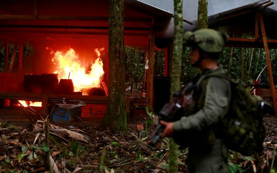 Soldado assiste a um laboratório numa área rural ser incendiado (Foto:  John Vizcaino/REUTERS)