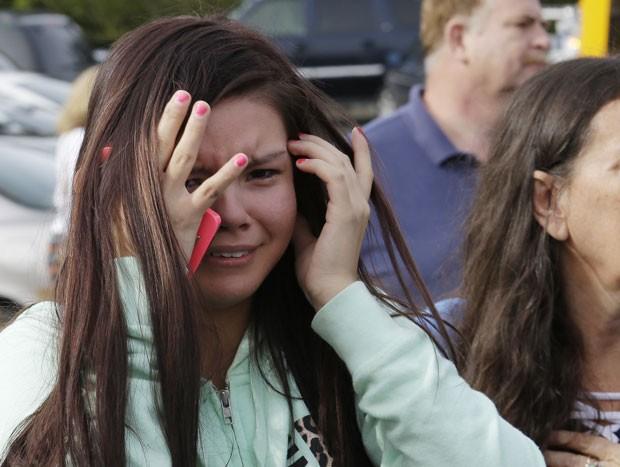 Jovem chora em igreja para onde parte dos alunos da escola foram levados (Foto: AP/Ted Warren)