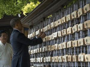 Presidente dos EUA, Barack Obama, coloca uma placa de madeira com oração em árvore no Santuário Meiji, em Tóquio (Foto: Jim Watson/ AFP)