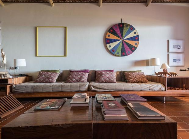 O sofá de madeira foi desenhado por Porfírio. A peça funciona como duas camas de solteiro em casos de superlotação na casa. As mesas laterais também fazem parte do móvel  (Foto: Daniel Mansur/Divulgação)