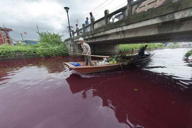 Homem navega por rio tingido de vermelho na província de Zheijang, na China. (Foto: AP)