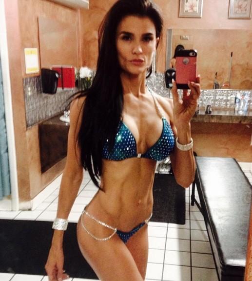 Mindi exibe os músculos diante de espelho