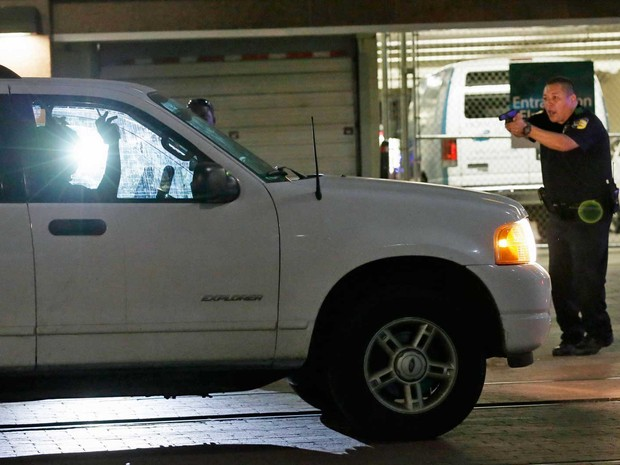 Policial para um motorista no centro de Dallas, após 'snipers' balearem agentes durante protesto (Foto: LM Otero / AP Photo)