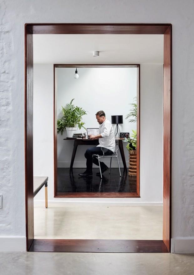 Localizado entre a sala de estar e a garagem, o espaço foi fechado por uma caixa de vidro. As molduras da porta e da janela são de kiaat, um tipo de madeira local. Nico está próximo à escrivaninha garimpada em uma loja vintage  (Foto: Greg Cox / Bureaux.CO.ZA)