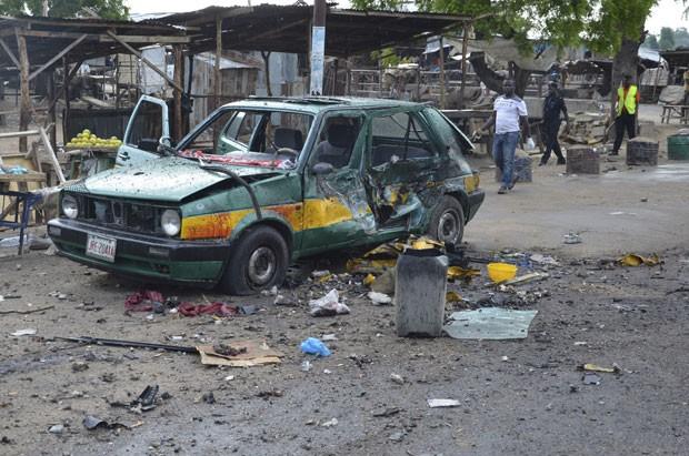 Pessoas passam por carro destruído em explosão nesta sexta-feira (31) em Maiduguri, na Nigéria (Foto: Jossy Ola/AP)