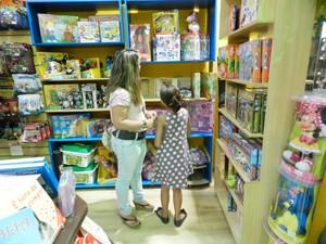 Mãe escolhendo brinquedo para presentear a filha (Foto: Anna Lúcia Silva/ G1)