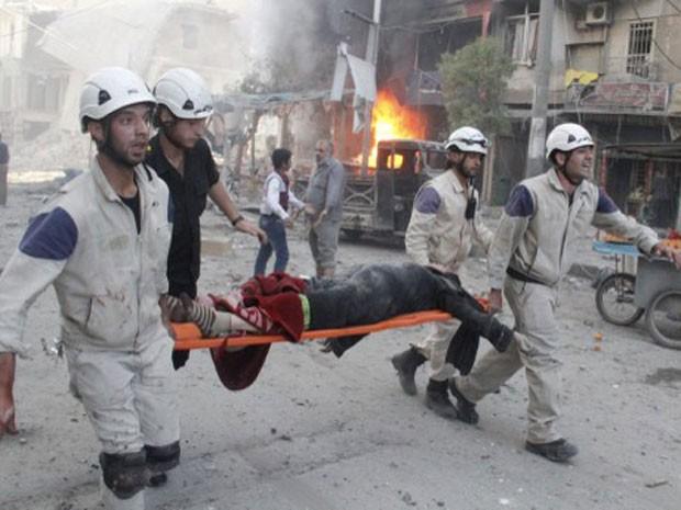 Socorristas ajudam no resgate de vítima de bombardeio em bairro de Aleppo, na Síria. Segundo ONG, ataque foi feito por militares pró-Assad (Foto: Khaled Khatib/Aleppo Media Centre/ AFP)