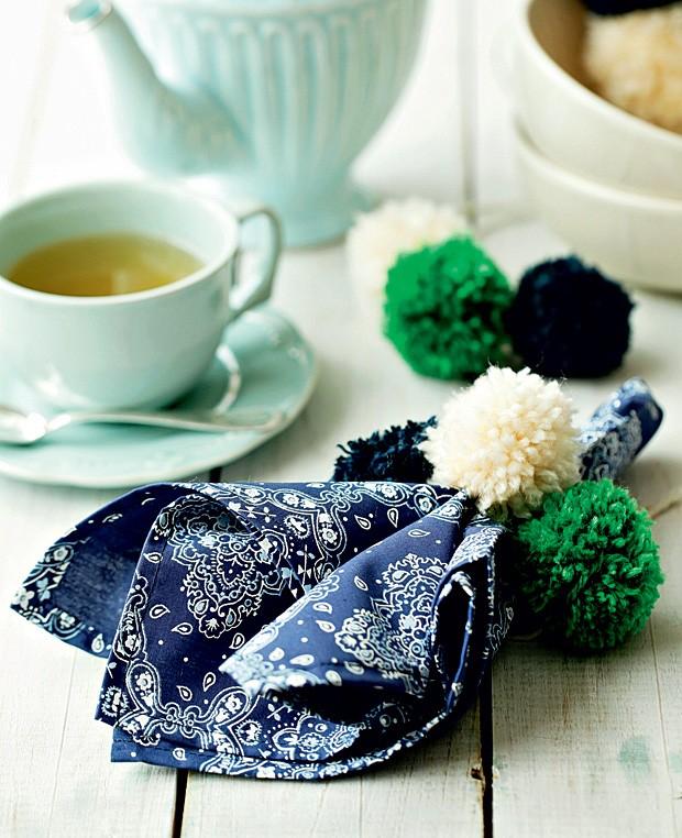 Como cozinha é um dos nossos temas favoritos, dá para levar os pompons para a mesa também. Com um pedaço de linha ou barbante, junto uns quatro ou cinco e faça um anel de guardanapo. Dá para misturar cores, tons e combinar com o resto da louça. (Foto: Elisa Correa/Editora Globo)
