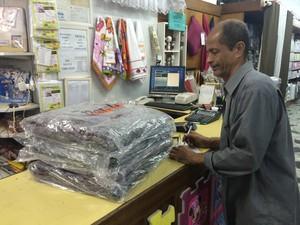 O vendedor Jorge Luiz comemora o aumento da venda de cobertores de doação por causa das baixas temperaturas no Rio de Janeiro (Foto: Cristiane Caoli / G1)