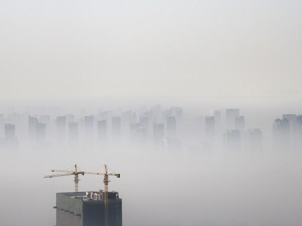 Prédio em construção é visto em meio a fumaça de poluição em Shenyang, em 21 de novembro (Foto: Jacky Chen/Reuters)