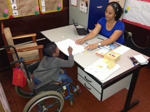 Professora Thiciane Pinheiro ensinando aluno deficiente (Foto: John Pacheco/G1)