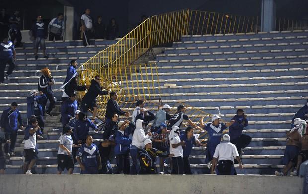 Confusão Torcida do Velez Sarsfield pula a barreira no jogo contra o Penarol (Foto: AFP)