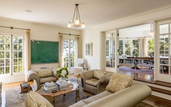 A sala de estar é ampla e as janelas são todas de vidro, com vista para os grandes jardins (Foto: Reprodução)