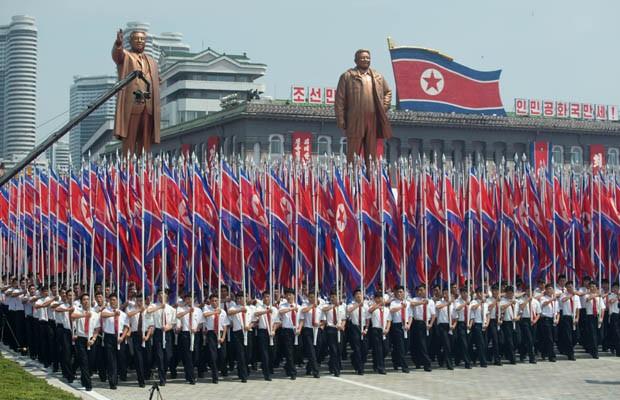 Norte-coreanos agitam bandeiras e carregam estátuas dos ex-líderes Kim Il-Sung e Kim Jong-Il em Pyongyang, durante desfile militar pelo 60º aniversário do armistício (Foto: AFP PHOTO / Ed Jones)