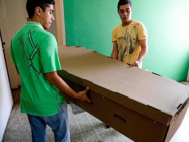Homens carregam um caixão feito de papelão em Barquismeto, na Venezuela (Foto: Federico Parra/AFP)