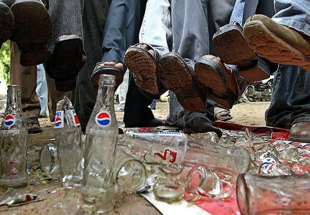 Manifestantes pisam sobre garrafas de Pepsi Cola e Coca Cola durante protesto pela proibição de refrigerantes na Índia
